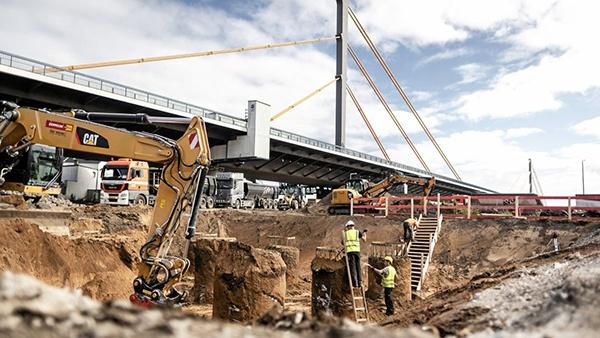 AVG Baustoffe Goch is tot en met 2027 ten behoeve van de realisatie van acht rijstroken voor een efficiëntere snelweg en de vervangingsconstructie van de Rijnbrug Duisburg-Neuenkamp, zowel voor de aanvoer van bulkgoederen en grond, als voor de overname, afvoer en verwijdering van grond en stoffen van verschillende verontreinigende klassen, verantwoordelijk. Evenals voor de organisatie van de bouwplaatslogistiek met actieve ondersteuning van AVG Transport. - Bis einschließlich 2027 ist AVG Baustoffe Goch, zur Realisierung von acht Fahrstreifen für eine leistungsfähigere Autobahn und Ersatzneubau der Rheinbrücke Duisburg-Neuenkamp, für die Lieferung von Schüttgütern und Böden sowie Übernahme, Abfuhr und Entsorgung von Böden und Stoffen unterschiedlicher Schadstoff klassen, verantwortlich. Sowie die Organisation der Baustellenlogistik mit tatkräftiger Unterstützung der AVG Transport.